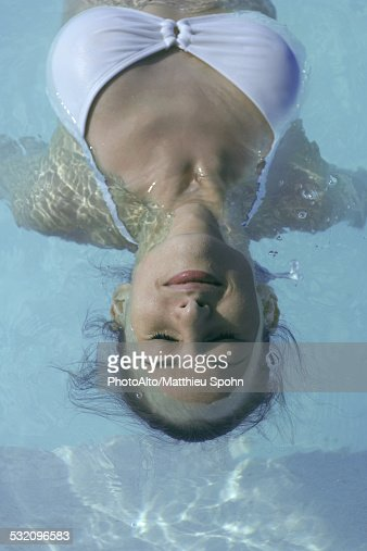 young woman floating in swimming pool eyes closed stock photo getty images