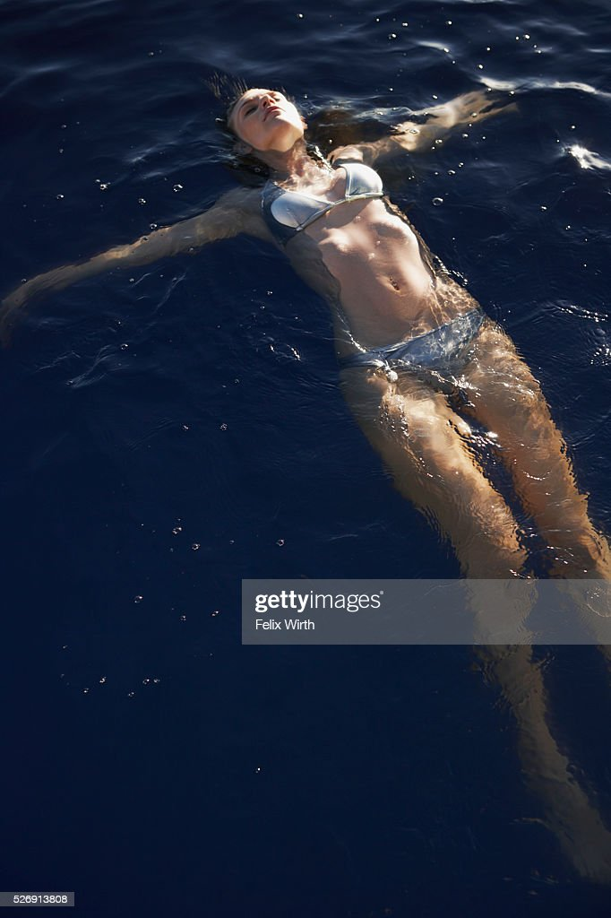 Young woman floating in swimming pool : Stock Photo