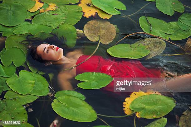 Young woman floating on water in the swamp
