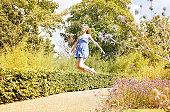 Young woman floating through a wild summer garden