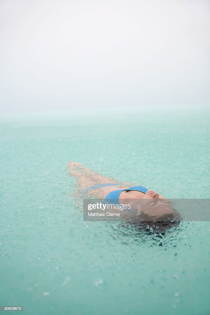 young woman floats in lagoon while it rains : Stock Photo