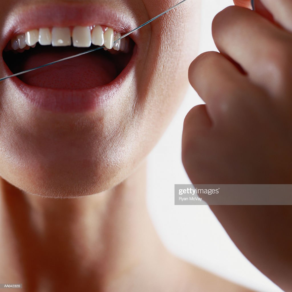 Young woman flossing her teeth, close-up