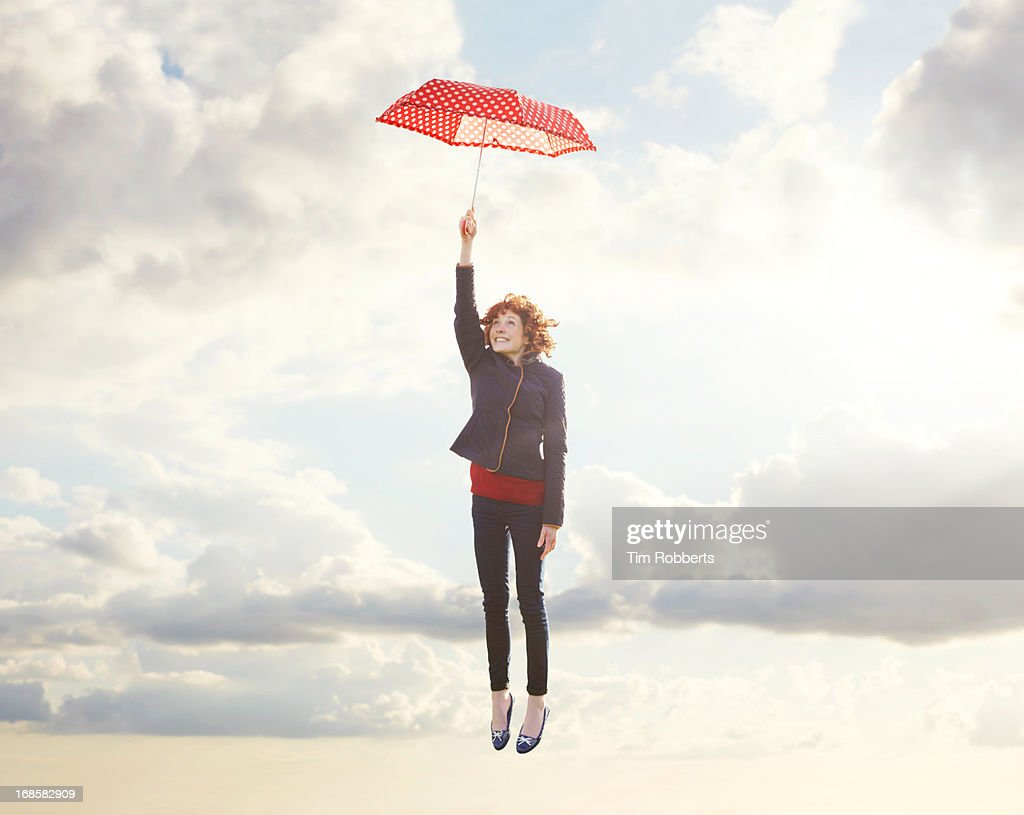 Young woman flying with umbrella. : Stock Photo