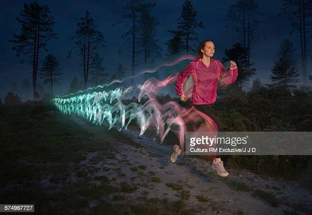 Young woman followed by light trails running on forest dirt track at night