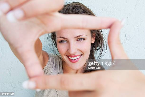Young woman framing herself with her hands