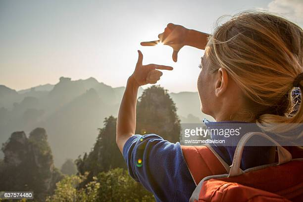 Young woman framing mountain landscape with hands