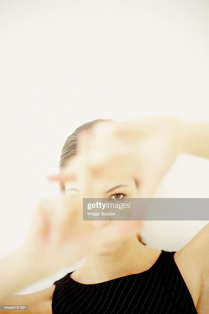 A young woman framing part of her face with hands showing her left eye