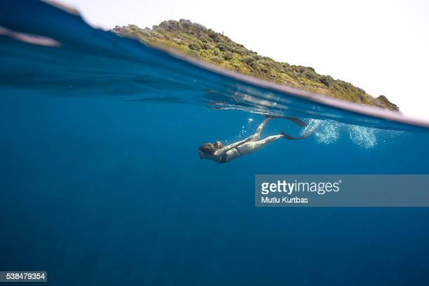 Young woman free diving underwater split shot