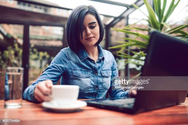 Young Woman Freelancer Working with Laptop Computer And Drinking Coffee in a City Cafe