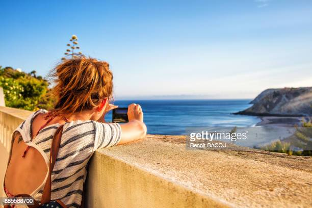 Young woman from behind, takes a photo with his smartphone on a low wall from the beach of Burgau, Algarve region, Portugal