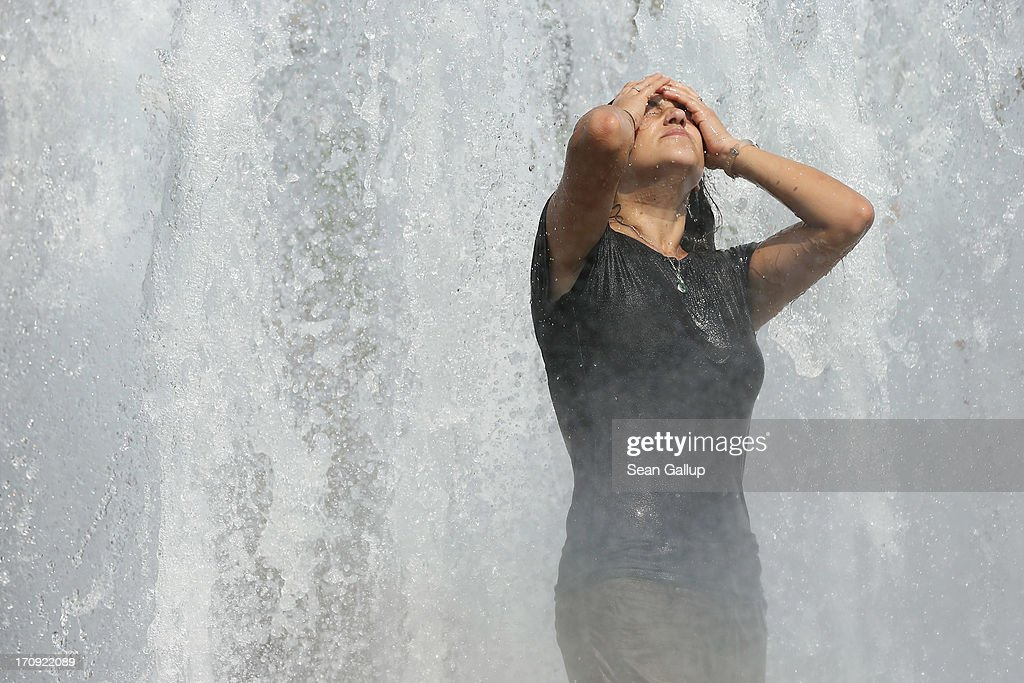 A young woman from Brazil cools off in a fountain on a scorching hot summer day in the city center on June 20, 2013 in Berlin, Germany. Central Europe is in the grips of a heat wave in which temperatures in some regions have reached up to 38 degrees celsius.
