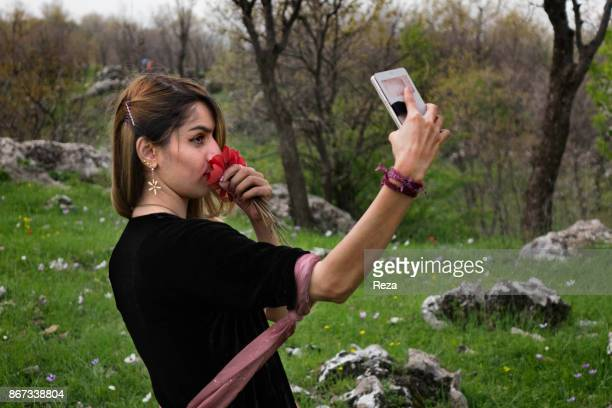 A young woman from Taher family takes a selfie during a picnic On the first day of spring following the tradition of new year in all the region...