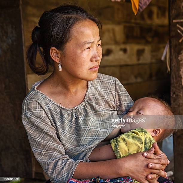 Young woman from the hill tribe breastfeeding her baby