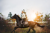 Young woman in riding gear galloping her chestnut horse through a field in the countryside in autumn