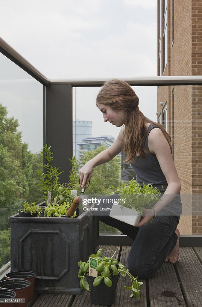 Young woman gardening on balcony