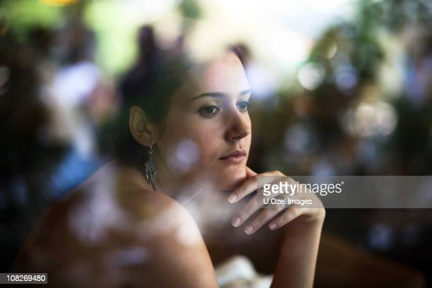 A young woman gazes out a reflective pane of glass