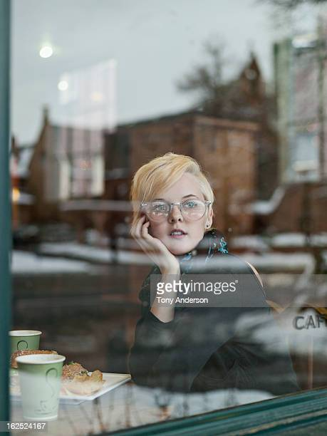 Young woman gazing out window of cafe