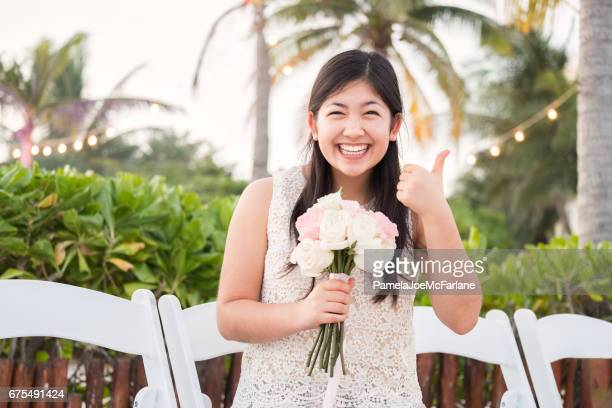 Young Woman Gesturing Thumbs Up, Holding Bouquet, in Tropical Garden