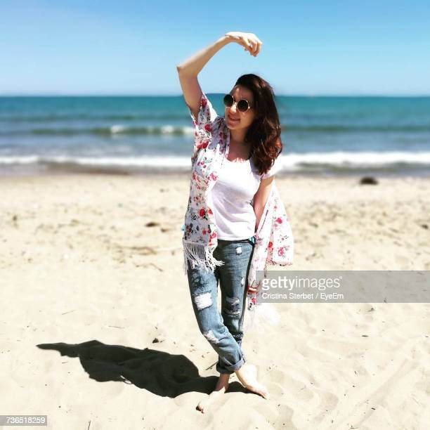 Young Woman Gesturing While Standing At Beach On Sunny Day