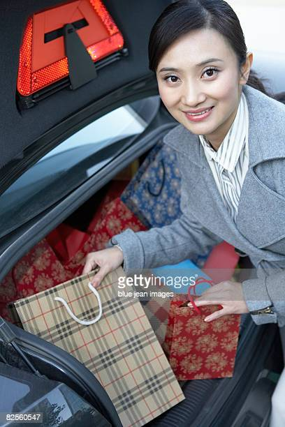 A young woman gets her shopping bags out of the car.