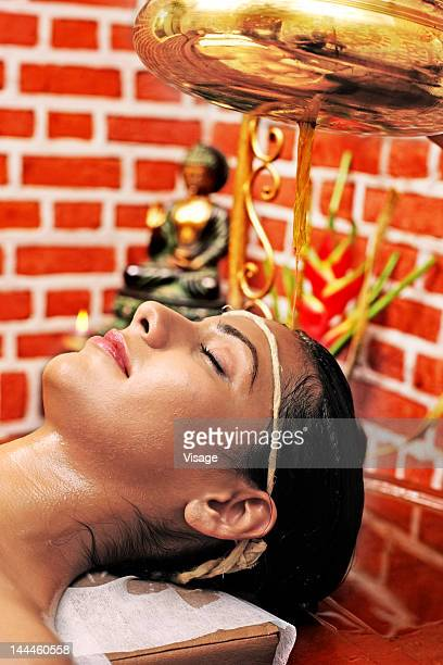 Young woman getting a Shirodhara treatment done