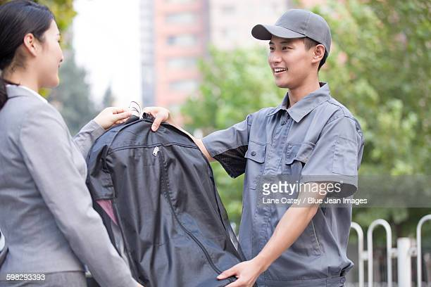 Young woman getting dry-cleaned clothes from delivery person
