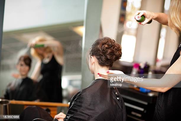 Jeune femme faire en coiffure chignon au Salon de beauté
