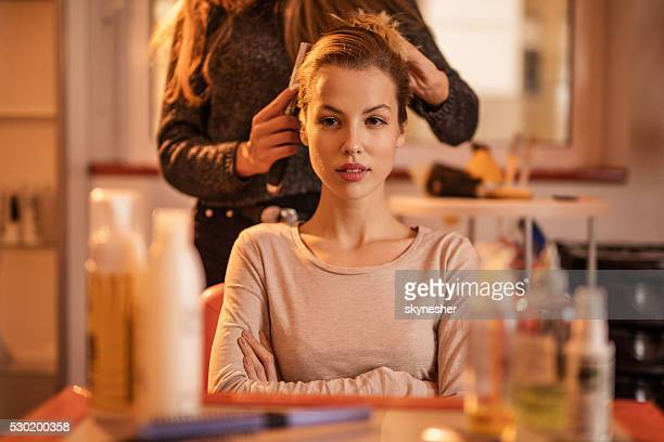 Young woman getting her hair styled at hair salon.