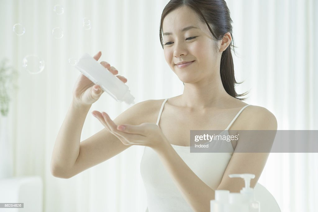 Young woman getting lotion to hand : Stock Photo