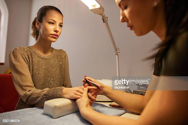 Giovane donna ottenere trattamento manicure in salone di bellezza.