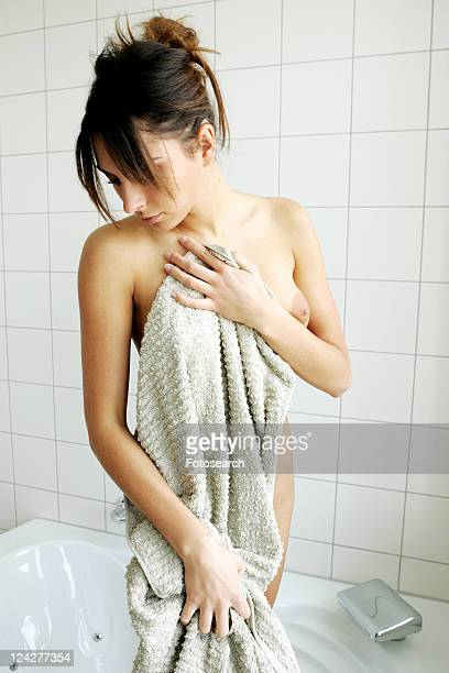 Young woman getting out of bathtub, rubbing herself dry with towel