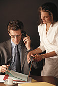 Young woman getting signature on document from businessman