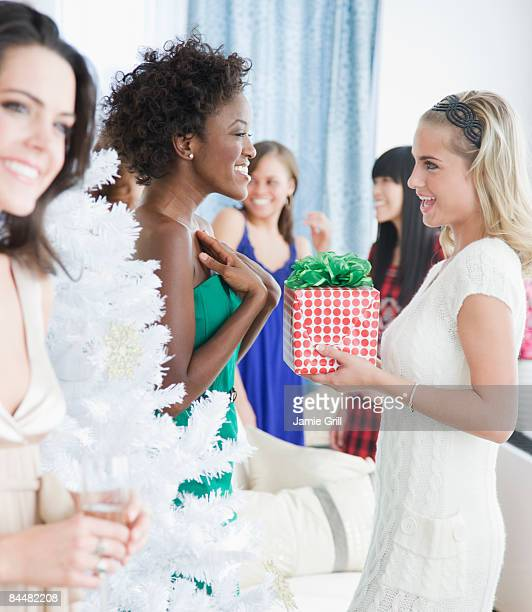 Young woman giving Christmas present to a friend