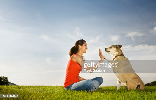 Young Woman Giving her dog a High Five.