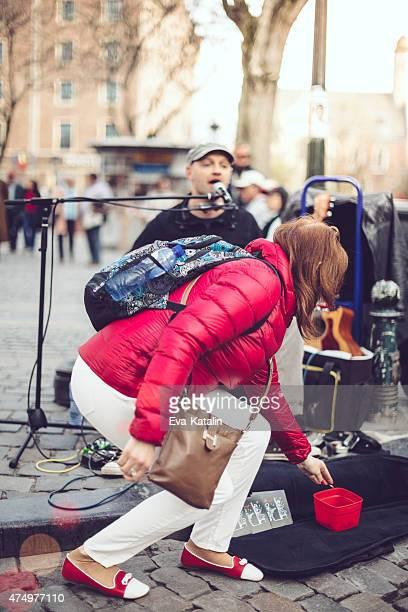 Jovem mulher dando dinheiro para um Músico de Rua