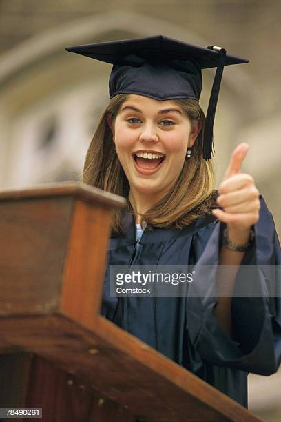Young woman giving thumbs up at graduation speech