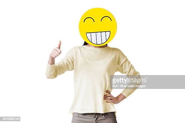 Young woman giving thumbs up with happy emoticon face in front of her face