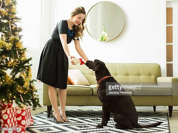 Young woman giving to dog Christmas present