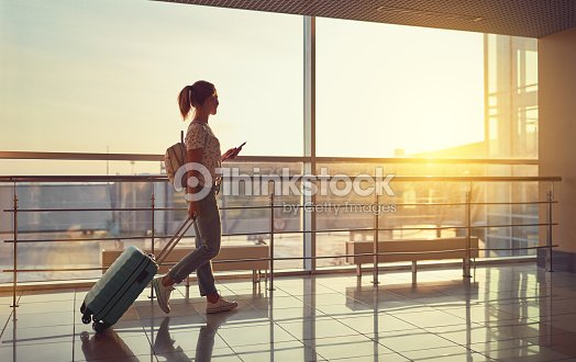young woman goes  at airport at window with suitcase waiting for plane : Stock Photo