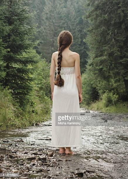 Jeune femme va pieds nus sur la rivière de montagne