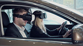 Young woman going for a test drive with the salesman in a new car as she makes a selection for her purchase, or she to pass virtual exam for driver license using virtual reality glasses.