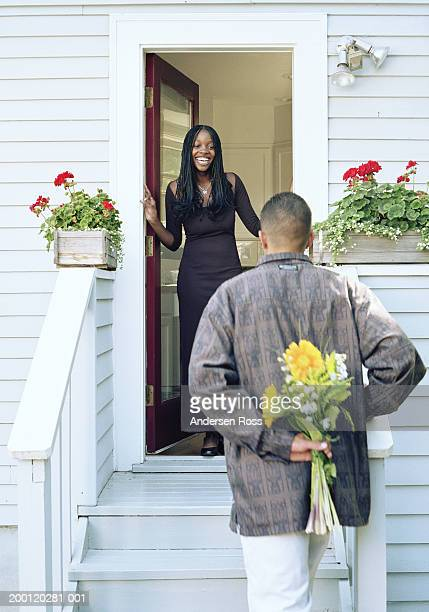 Young woman greeting young man from doorway, man hiding flowers
