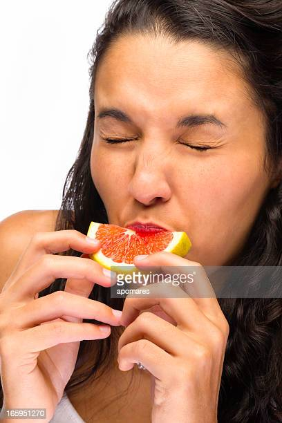 Young woman grimacing face while tasting sauer grapefruit
