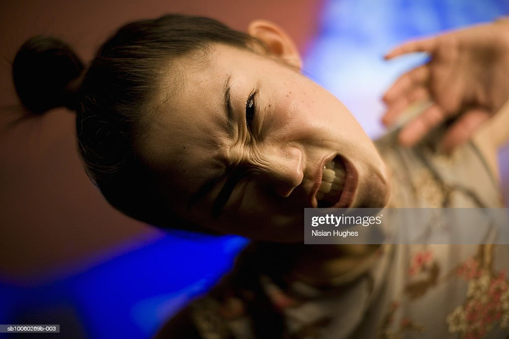Young woman grimacing, portrait : Stock Photo