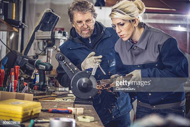 Young Woman Grinding Metal in Mechanical Workshop