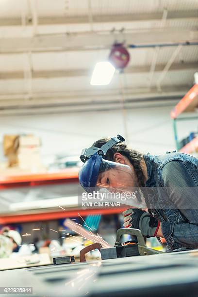 Young woman grinding metal