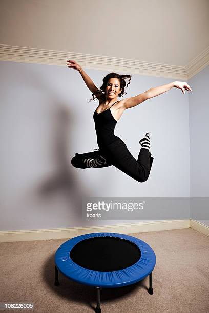 Young woman gymnast on a trampoline in a room
