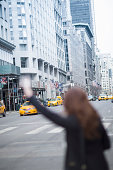 Young woman hailing a yellow cab, New York, USA