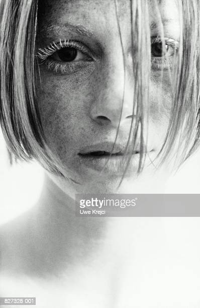 Young woman (14-16), hair falling over eyes, portrait (B&W)