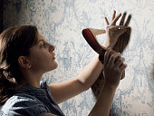 Young woman hammering nail into wall with shoe